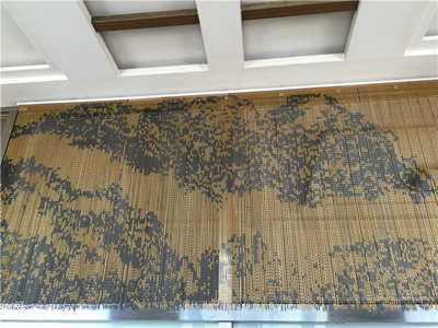 Chain screen is hanging in the room as decoration with mountain pattern.