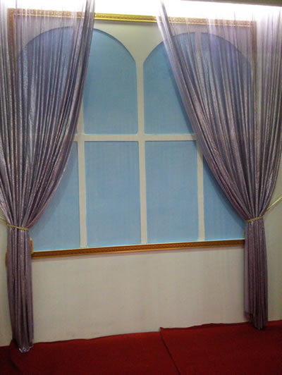 A scale mesh curtain in purple is collected in two parts as cloth curtain.