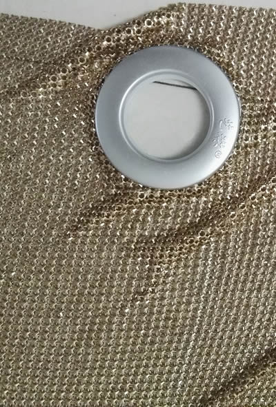 The detail of scale mesh curtain's eyelet, and the curtain is golden.