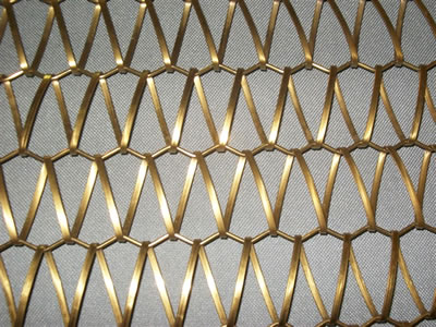 A piece of wire mesh belt, composed by round rod and flat spiral wire, in gold color on the white background.