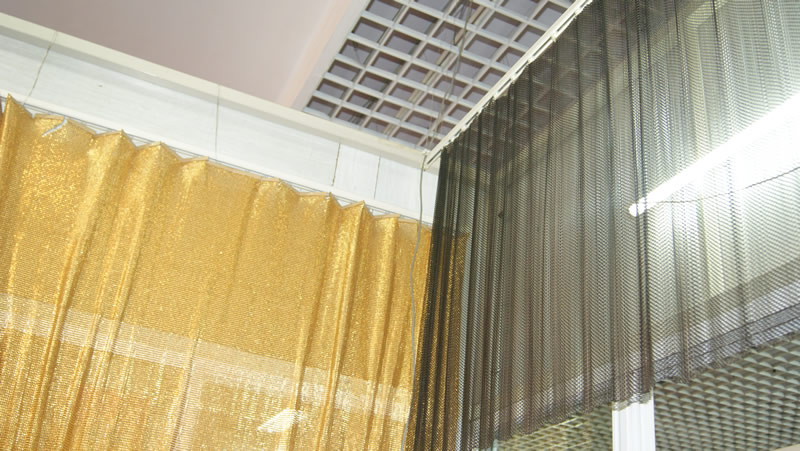 The scale mesh curtain is hanging on the ceiling as a room decoration, and beside it there is a metal coil drapery decorating the room, too.