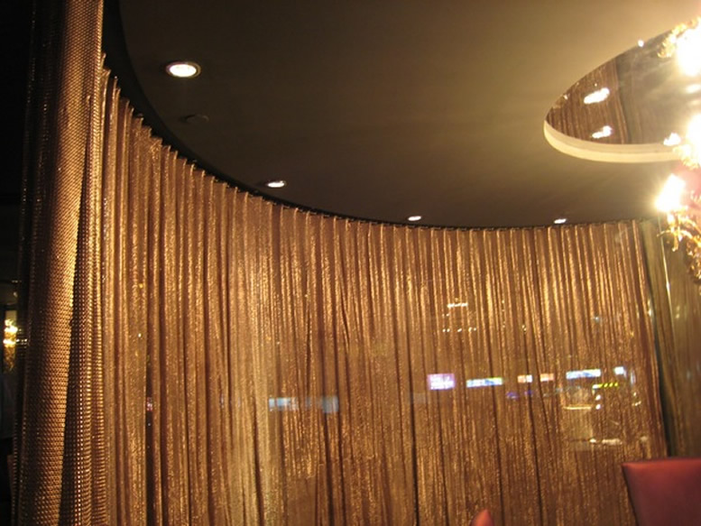There is a scale mesh curtain in copper color hanging on the ceiling as a space divider, and there is a lamp in the hall.
