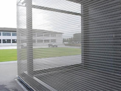 Wire mesh belt is as wall cladding, the outside of belt mesh is a grass yard and a white building.